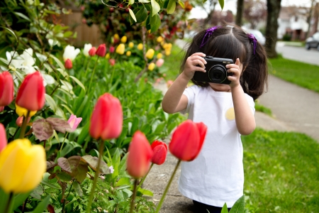 Young girl looking through viewfinder of her camera making a photo of spring flowers photo