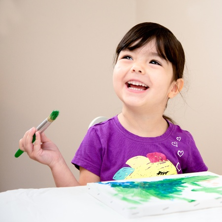 Toddler laughing as she paints a picture on a canvas
