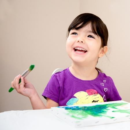 Toddler rire comme elle peint une image sur une toile