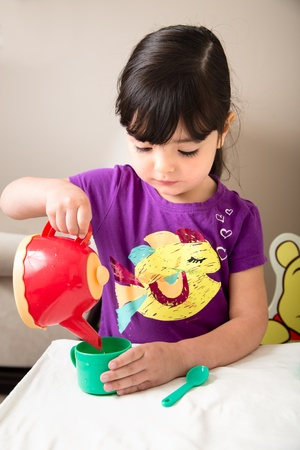 pours: Toddler Carefully Pours a Cup of Tea  Water