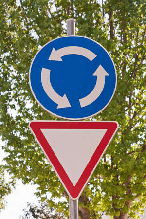 precedence: Roundabout  double sign with some trees on background