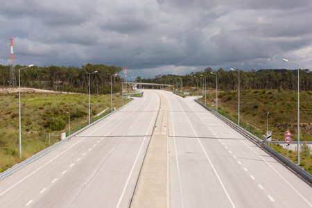 Upper view of an portuguese motorway against woods and cloudy sky photo