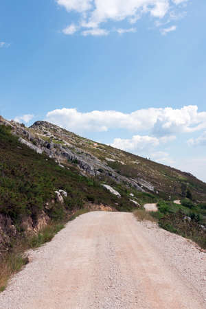 Emtpy gravel road through mounatin against blue sky and clouds Stock Photo - 9659901