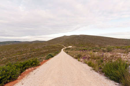 Emtpy gravel roads through mountains against cloudy sky Stock Photo