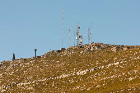 Communication antennas on a rocky hill photo