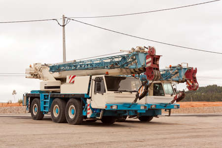a two wheeled vehicle: Two auto cranes standing in a parking lot Stock Photo