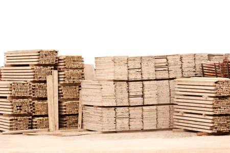 Pila de tablones de madera en el suelo de grava contra la pared blanca Foto de archivo