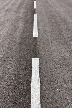 Vertical composition of tarmac road and white marks Stock Photo