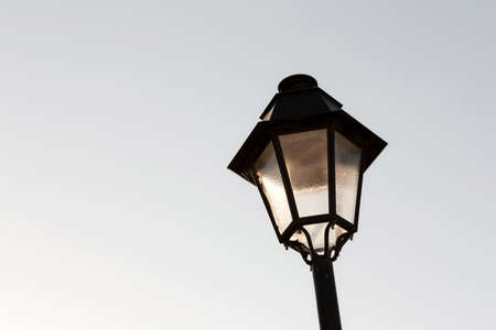 Street lamp lit by the sun against clear blue sky Stock Photo - 10555081