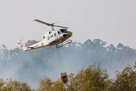 POMBAL, PORTUGAL - OCTOBER 1 : Fire rescue heavy helicopter, with water bucket, preparing for water scooping to combat a fire in Pombal October 1, 2011 in Pombal, PORTUGAL Stock Photo - 10839083