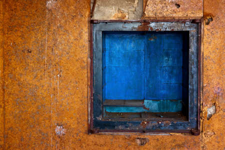 dirty old orange wall with small blue enclosure Stock Photo - 10861129