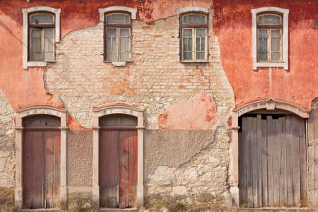 old building facade: Abandoned facade with wood windows and doors in Portugal Stock Photo