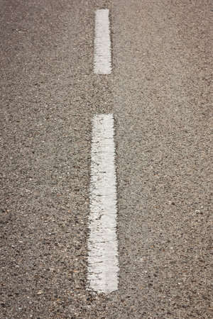 Closeup perspective of white marks in a asphalt road photo