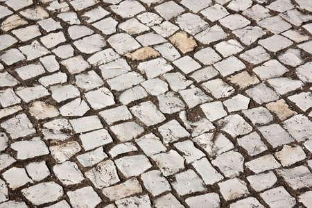 Portuguese cobblestone sidewalk made of cubic stones photo