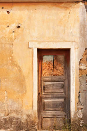 Old ruined facade with just an wooden door Stock Photo