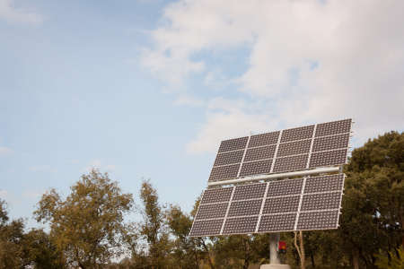 small solar panel against trees and sky photo