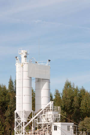 processing silos of a concrete factory against forest and blue sky Stock Photo - 11532599