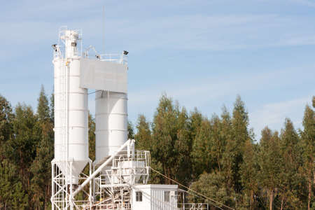 processing silos of a concrete factory against forest and blue sky Stock Photo - 11532601