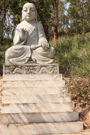 Marble buddha statue exhibited in an public garden photo