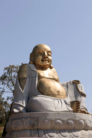 Laughing bronze buddha statue exhibited in an public garden photo