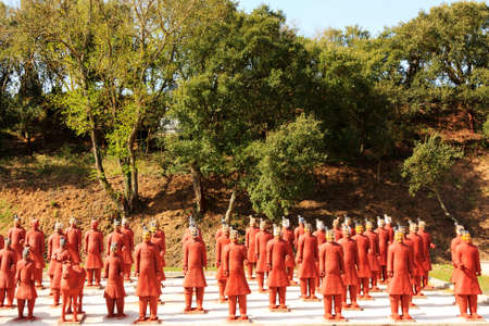 Several red terracotta soldiers exhibited in an public garden