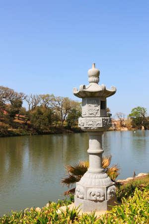 An Japanese Stone Lantern on lake side, in public park