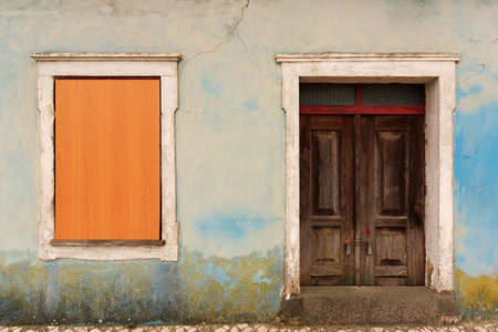 Abandoned facade with covered window and old door Stock Photo - 13043590