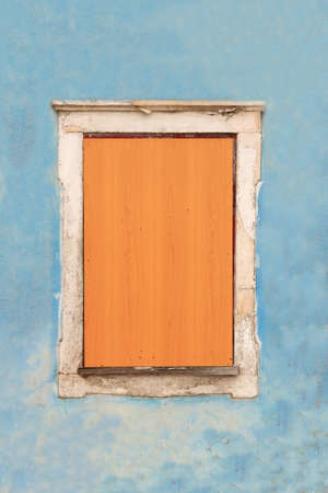 An window covered with wood on aged facade