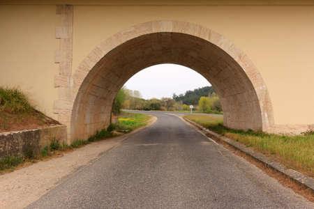 Man made road tunnel against woods and cloudy sky Stock Photo