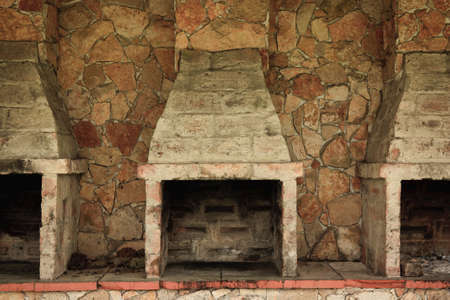 Empty and Fireless brick ovens against stone wall photo