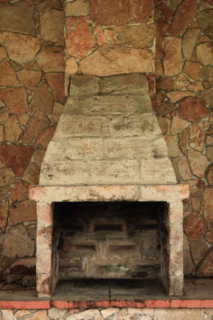 Empty and Fireless brick oven against stone wall photo