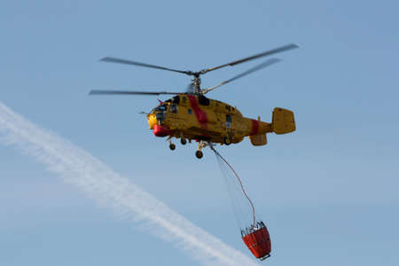 drain fly: AVELAR, PORTUGAL - JULY 7 : Fire rescue heavy helicopter, with water bucket, preparing for water scooping to combat a fire in Avelar July 7, 2012 in Avelar, Portugal