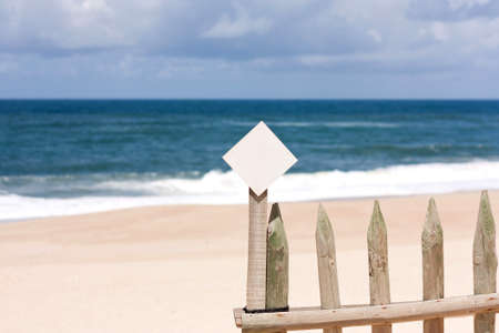 Little notice board, on wood fence, against beach and sea. Shallow DOF