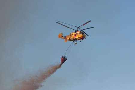 POMBAL, PORTUGAL - JULY 15: Fire rescue heavy helicopter dropping water on a wildfire, in Pombal, Portugal on July 15, 2012