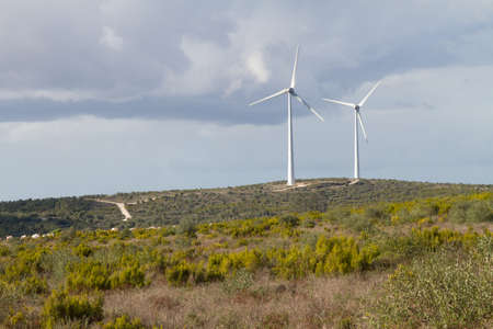 An pair of windmills turbines on the top of an hill Stock Photo - 16587053