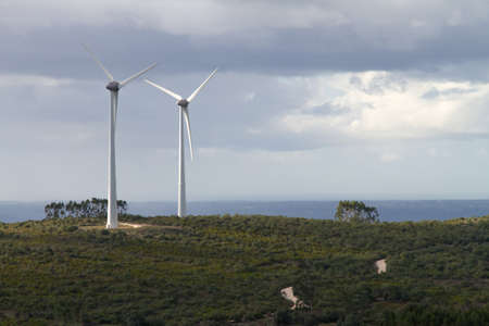 An pair of windmills turbines on the top of an hill photo