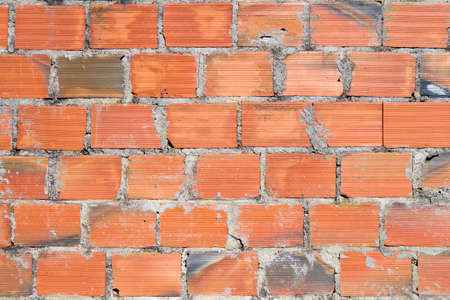 flawed: Flawed wall made of orange bricks for background
