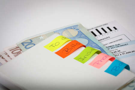 bills to pay with some post-it and banknotes inside an book Stock Photo - 17446432