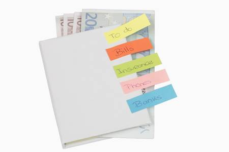 bills to pay with some post-it and banknotes inside an book photo