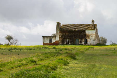 Abandoned Farm house over green field on cloudy day photo