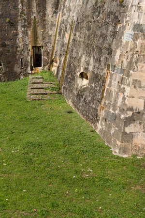 Grassy passage to a small entrance on stone building
