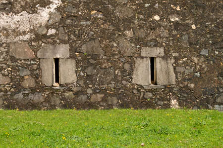 Stone ancient facade windows with front grass ground