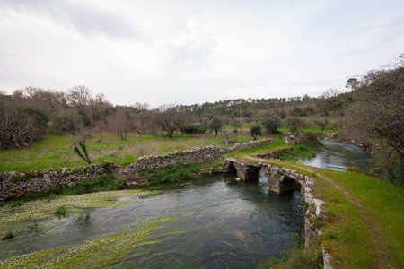 Stone bridge over small river against rural landscape