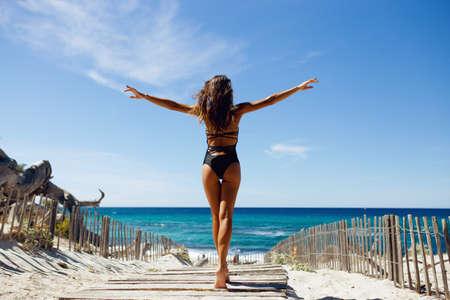 Rückansicht der jungen Frau mit Bikini am Strand. Junge Frau im Badeanzug, die mit erhobenen Händen an der Küste steht. Korsika, Frankreich.