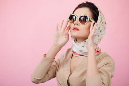 Style magnifique d'une jeune femme vêtue de vêtements élégants, posant sensuelle en studio, isolée sur fond rose. Banque d'images