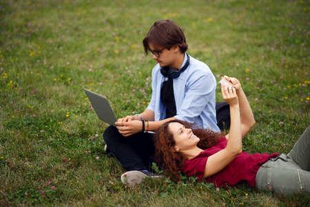 Bild von netten jungen Leuten, Freunden, sitzend auf grünem Gras in einem öffentlichen Park, isoliert von einer wunderschönen Natur, Sonnenuntergang. Bildungskonzept. Schöner Tag für ruhige Arbeiten im Freien.
