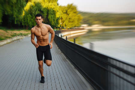 Image of a athlete young man with naked torso, Morning run in open air in urban park, early sunny summer morning. Sports lifestyle concept. 版權商用圖片