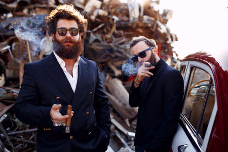 A two bearded men in a classic suits,hairstyle, black sunglasses, smoking cigars and looks seriously at camera.Bad rich boys on iron dump background.Gentlemen's club.Horizontal view.