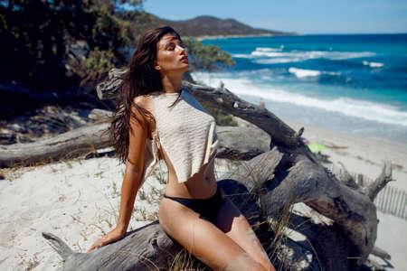 Ein Mädchen mit perfektem heißen Körper am Strand, isoliert auf einem meerblauen Wellen und weißem Sandhintergrund.