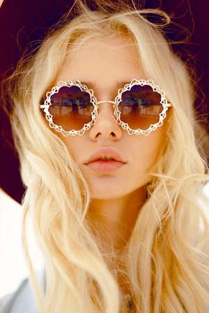 Retrato de belleza de una linda rubia con anteojos florales redondos, labios grandes, cabello ondulado y sombrero burdeos, mirando sensual a cámara. Vista vertical